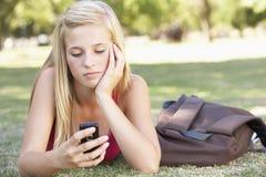 Estudiante adolescente femenino infeliz With Mobile Phone en parque Fotos de archivo