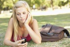 Estudiante adolescente femenino infeliz With Mobile Phone en parque Imagen de archivo