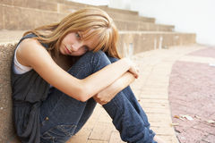 Estudiante adolescente femenino infeliz que se sienta afuera Foto de archivo libre de regalías