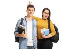 Estudiante adolescente femenino pranking un estudiante adolescente masculino con los oídos del conejito Fotos de archivo libres de regalías