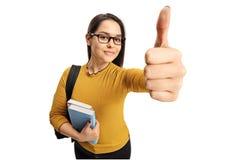 Estudiante adolescente femenino que hace un pulgar encima del gesto Foto de archivo libre de regalías