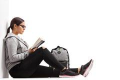 Estudiante adolescente femenino que lee un libro Fotos de archivo libres de regalías