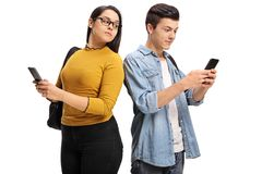 Estudiante adolescente femenino que mira a escondidas en el teléfono de un estudiante adolescente masculino Imagen de archivo