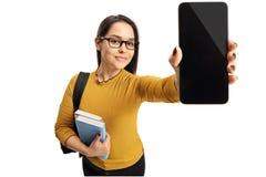Estudiante adolescente femenino que muestra un teléfono Foto de archivo libre de regalías