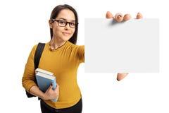 Estudiante adolescente femenino que muestra una tarjeta en blanco Fotografía de archivo libre de regalías