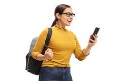 Estudiante adolescente femenino que usa un teléfono y gesticulando felicidad Foto de archivo