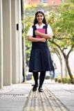 Estudiante adolescente femenino Walking On Sidewalk imagenes de archivo