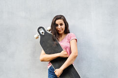 Estudiante adolescente hermoso con el monopatín contra el muro de cemento Foto de archivo libre de regalías