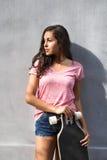 Estudiante adolescente hermoso con el monopatín contra el muro de cemento Fotografía de archivo