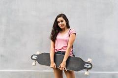 Estudiante adolescente hermoso con el monopatín contra el muro de cemento Imagen de archivo