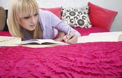 Estudiante adolescente hermoso Writing In Book en cama Foto de archivo