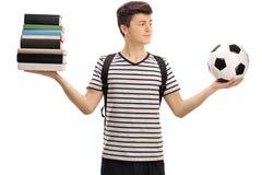 Estudiante adolescente indeciso que sostiene fútbol y la pila de libros Foto de archivo libre de regalías