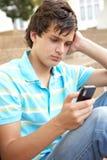 Estudiante adolescente infeliz afuera usando el teléfono móvil Fotos de archivo libres de regalías