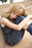 Estudiante adolescente infeliz que se sienta afuera Fotografía de archivo libre de regalías