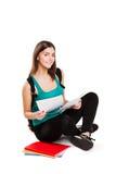Estudiante adolescente joven que se sienta en piso con la mochila Imagen de archivo