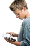 Estudiante adolescente joven que trabaja en la tableta. Foto de archivo libre de regalías