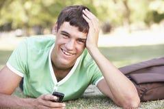 Estudiante adolescente masculino feliz With Mobile Phone en parque Imagen de archivo