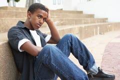 Estudiante adolescente masculino infeliz que se sienta afuera Foto de archivo libre de regalías