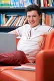 Estudiante adolescente masculino With Laptop Working en biblioteca Imagenes de archivo