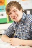 Estudiante adolescente masculino que estudia en sala de clase Foto de archivo libre de regalías