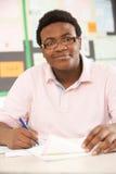 Estudiante adolescente masculino que estudia en sala de clase Fotos de archivo