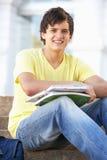 Estudiante adolescente masculino que se sienta en pasos de progresión de la universidad Fotos de archivo libres de regalías