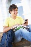 Estudiante adolescente masculino que se sienta en pasos de progresión de la universidad Foto de archivo