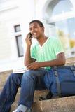 Estudiante adolescente masculino que se sienta en pasos de progresión de la universidad Imagen de archivo libre de regalías