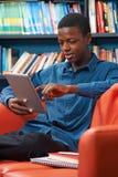 Estudiante adolescente masculino Using Digital Tablet en biblioteca Imágenes de archivo libres de regalías