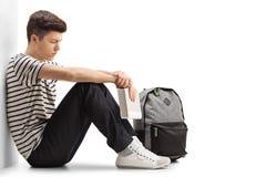 Estudiante adolescente pensativo que se inclina contra una pared Imagen de archivo