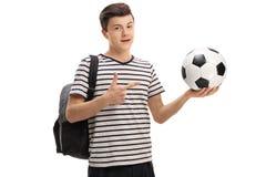 Estudiante adolescente que celebra un fútbol y señalar Foto de archivo libre de regalías