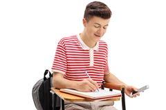 Estudiante adolescente que engaña en una prueba con un teléfono Imagen de archivo libre de regalías