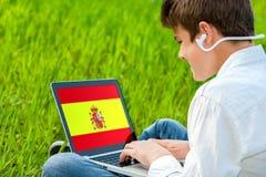Estudiante adolescente que hace curso español en el ordenador portátil. Imagenes de archivo