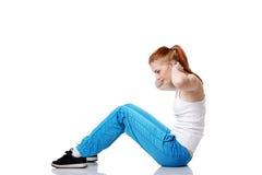 Estudiante adolescente que hace ejercicios en el suelo. Foto de archivo