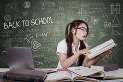 Estudiante adolescente que lee un libro de texto Imagen de archivo