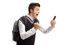 Estudiante adolescente que mira un teléfono y que gesticula felicidad Fotografía de archivo libre de regalías