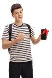 Estudiante adolescente que muestra el teléfono con la cinta roja y señalar Fotografía de archivo libre de regalías