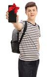 Estudiante adolescente que muestra el teléfono envuelto con la cinta roja como presente Imagen de archivo libre de regalías