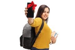 Estudiante adolescente que muestra un teléfono envuelto con la cinta roja como a pre Imagenes de archivo