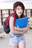 Estudiante adolescente que se coloca en la biblioteca Fotografía de archivo