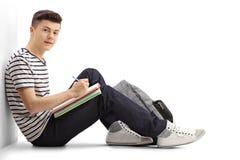 Estudiante adolescente que se inclina contra una escritura de la pared en un cuaderno Fotos de archivo