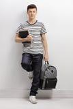 Estudiante adolescente que se inclina contra una pared gris Fotografía de archivo