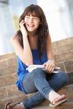 Estudiante adolescente que se sienta afuera en pasos de progresión de la universidad Fotografía de archivo