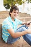 Estudiante adolescente que se sienta afuera usando el teléfono móvil Imagen de archivo
