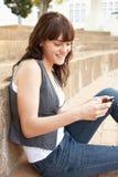 Estudiante adolescente que se sienta afuera usando móvil   Fotografía de archivo libre de regalías