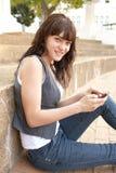 Estudiante adolescente que se sienta afuera usando móvil   Fotos de archivo