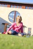 Estudiante adolescente que se sienta en la hierba fuera de la escuela Fotografía de archivo libre de regalías