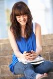 Estudiante adolescente que se sienta en pasos de progresión de la universidad Imagen de archivo