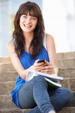 Estudiante adolescente que se sienta en pasos de progresión de la universidad Foto de archivo libre de regalías