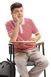 Estudiante adolescente que se sienta en una silla de la escuela y que toma notas Fotos de archivo libres de regalías